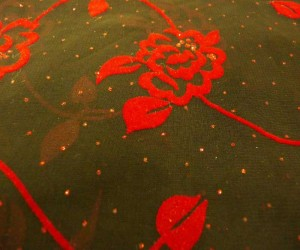"60""black sheer rayon with red flocked flowers with allover red sparkle"